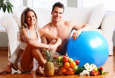 fitness and exercise at home picture of couple sitting near exercise ball in living room in front of couch
