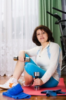 fitness at home theme picture of woman working out in her living room with dumbbells, red towel, and exercise machine in background